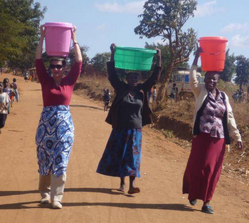 Gates carries bucket of water on her head
